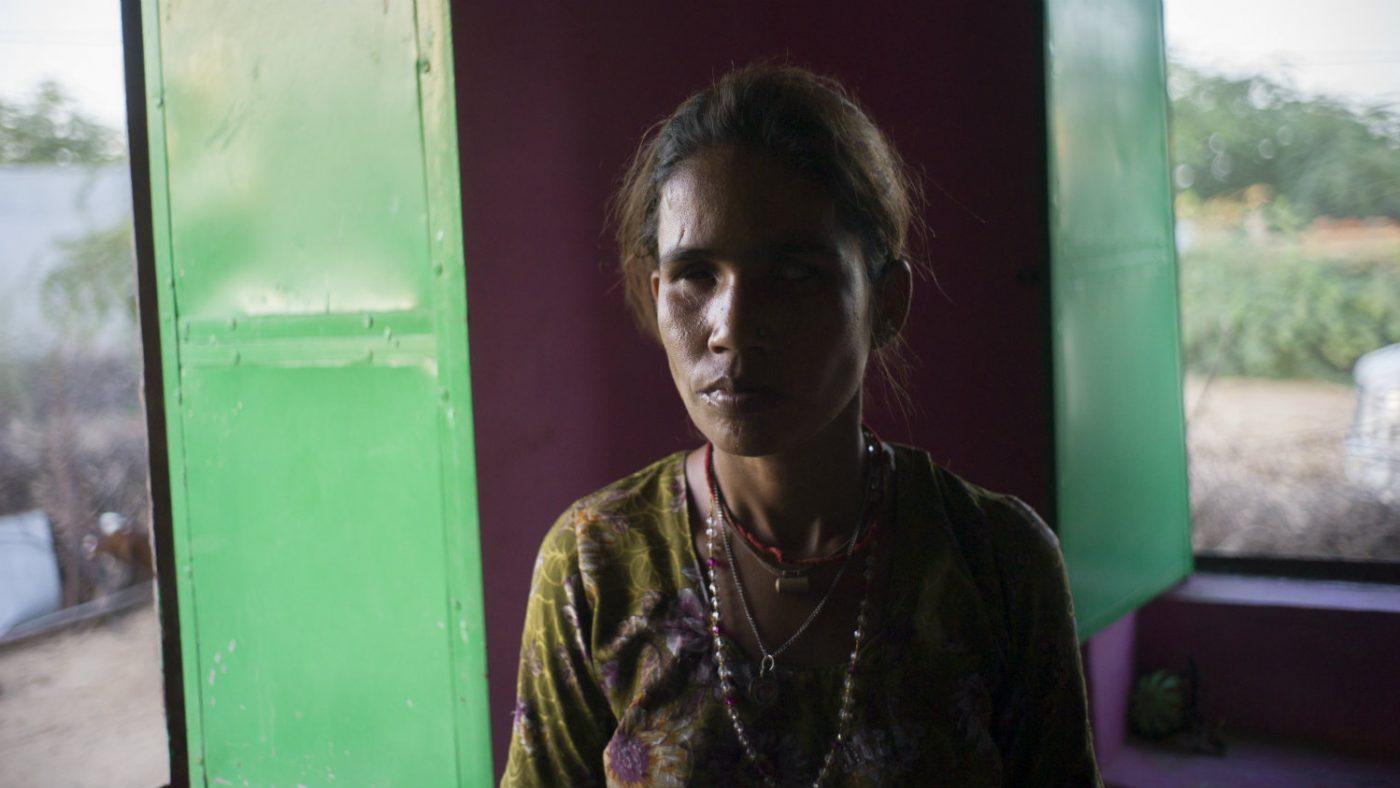 Dallu standing the doorway of her house.