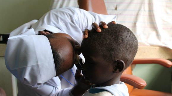 A child's eyes are examined by a nurse.
