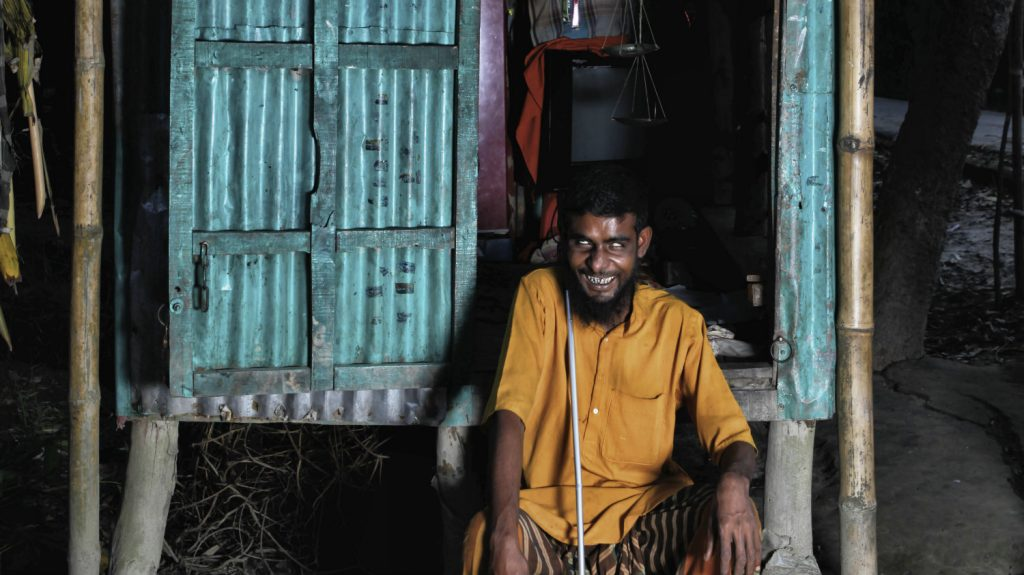 Hazrat smiles as he sits in his shop.