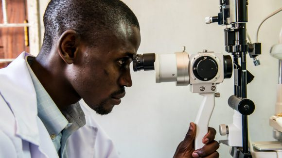 A health worker uses eye care equipment in Malawi.