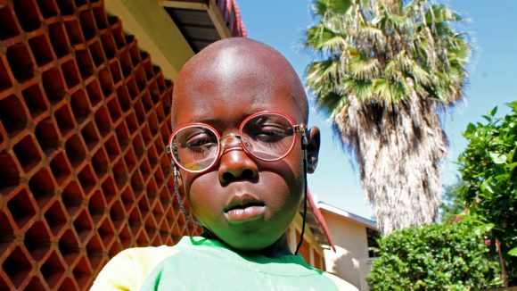 Ivan, a Ugandan child, wears his new spectacles.