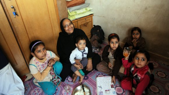 In Pakistan, a disabled mother sits with her large family.