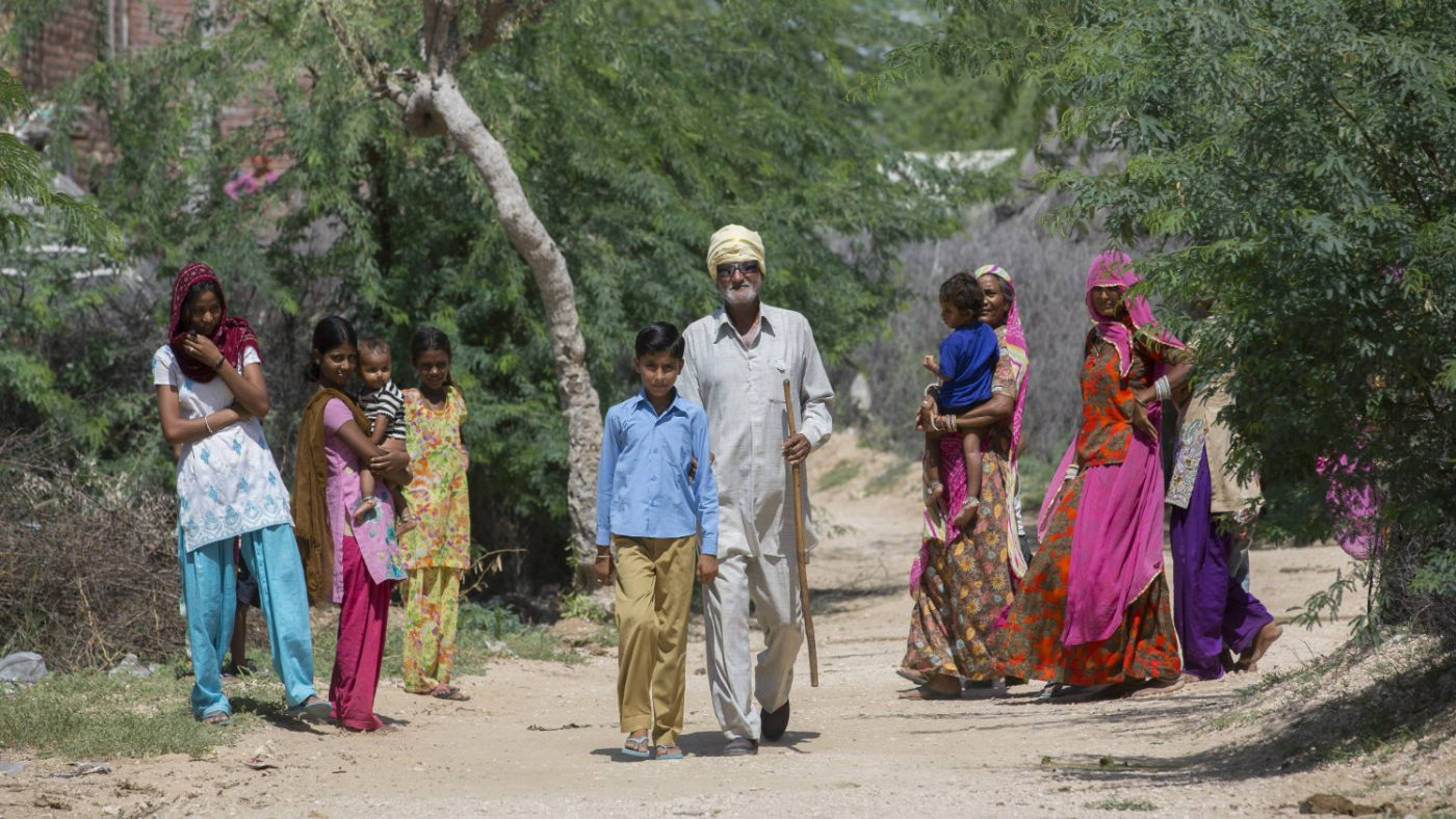Sankarlal walking in the community.