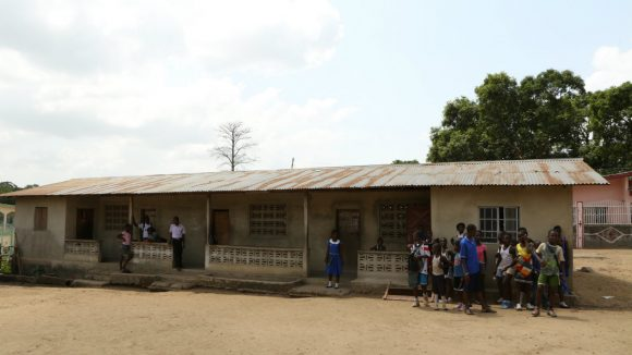 Children wait to start lessons outside a school in Sierra Leone.