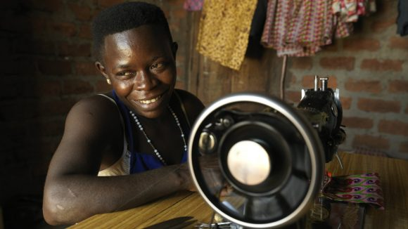 A Ugandan woman sewing clothes.