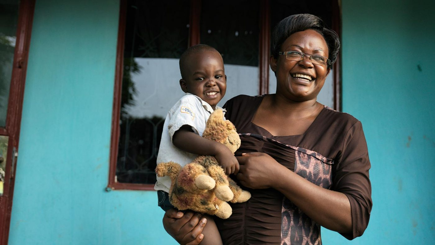 Edith smiles as she stands holding her young son.