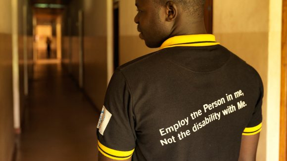 Atugonza shows off the back of his Sightsavers t-shirt, which features the words: 'Employ the person in me, not the disability with me'.
