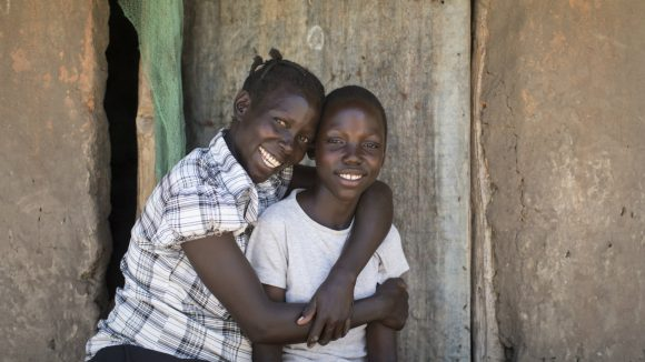 A Ugandan girl hugs her brother after a successful cataract operation.