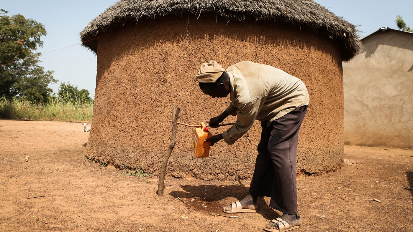 A man washes his hands outside a mud hut.