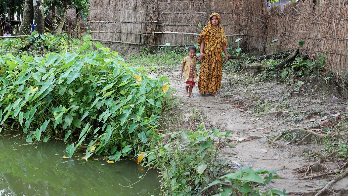 Aklima holds her mother's hand as they walk past a pond by her home.