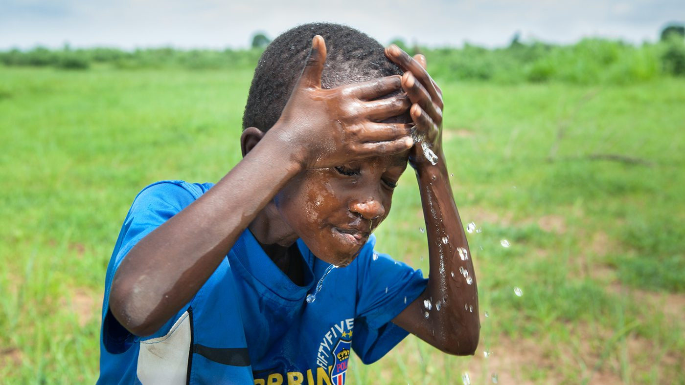A 12 year old boy washes his face.