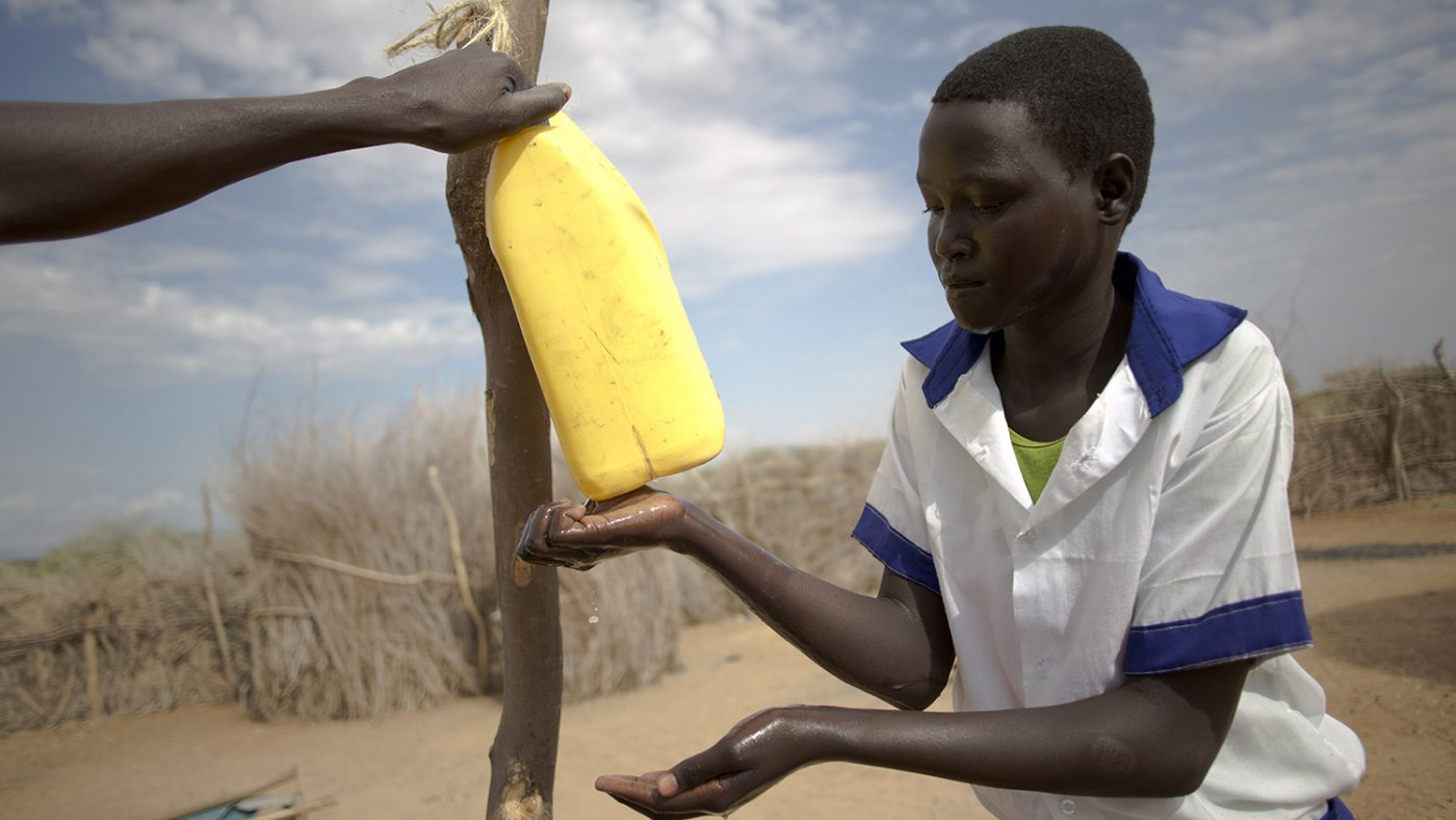 A girl is washing her hands under a yellow container.