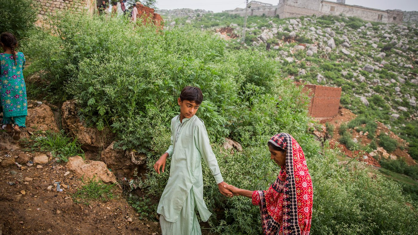 Kausar's son leads her up the hill towards their home.