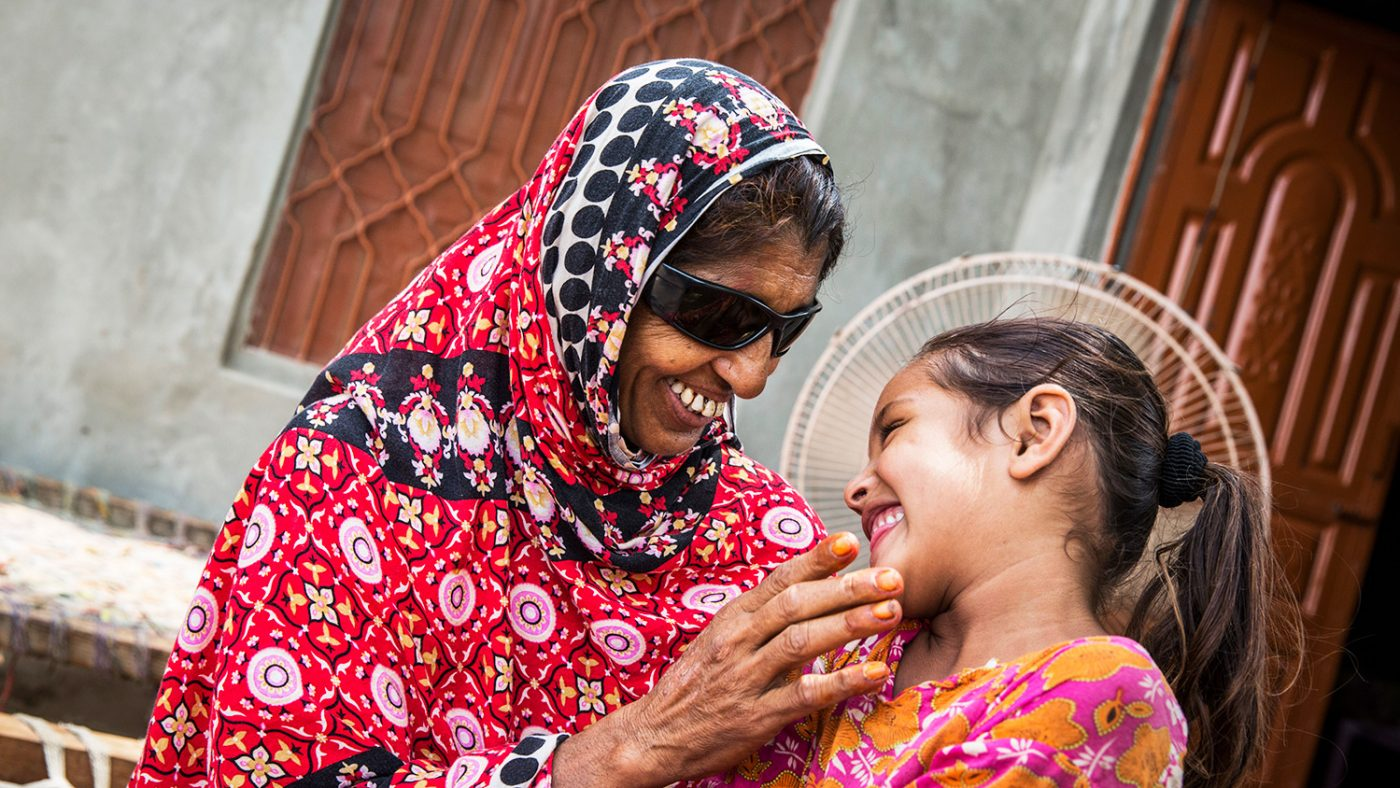 Kausar and her daughter happily smile at each other.