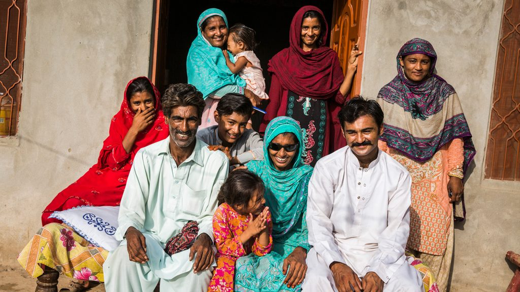 Kausar sits outside her home with her family, all posing for the camera.