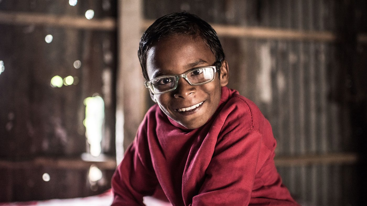 Photo of a young boy smiling with glasses on.