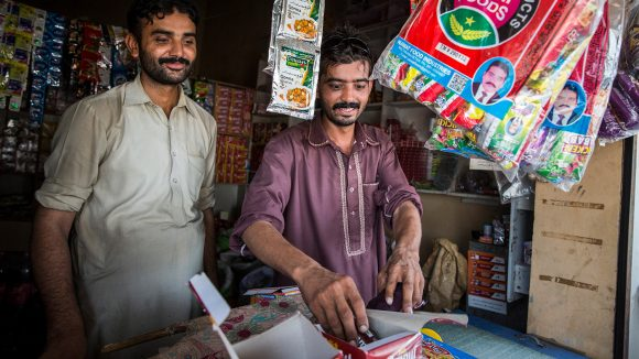 Murtaza picks sweets out of a box in a shop, while smiling.