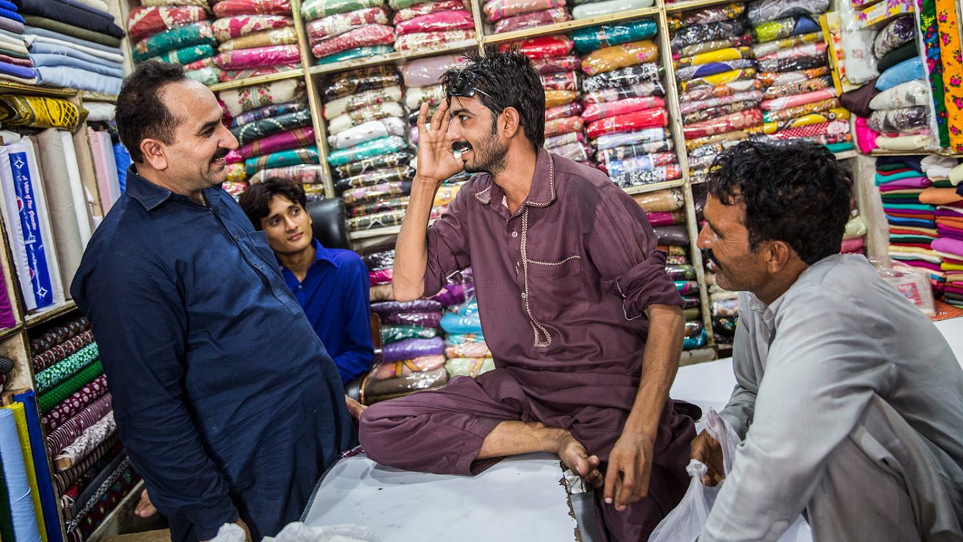 Murtaza talks to people in a shop.