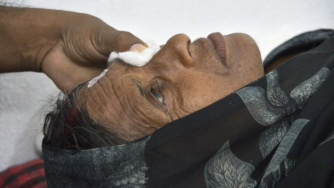 A dressing is applied to a woman's eye following cataract surgery.