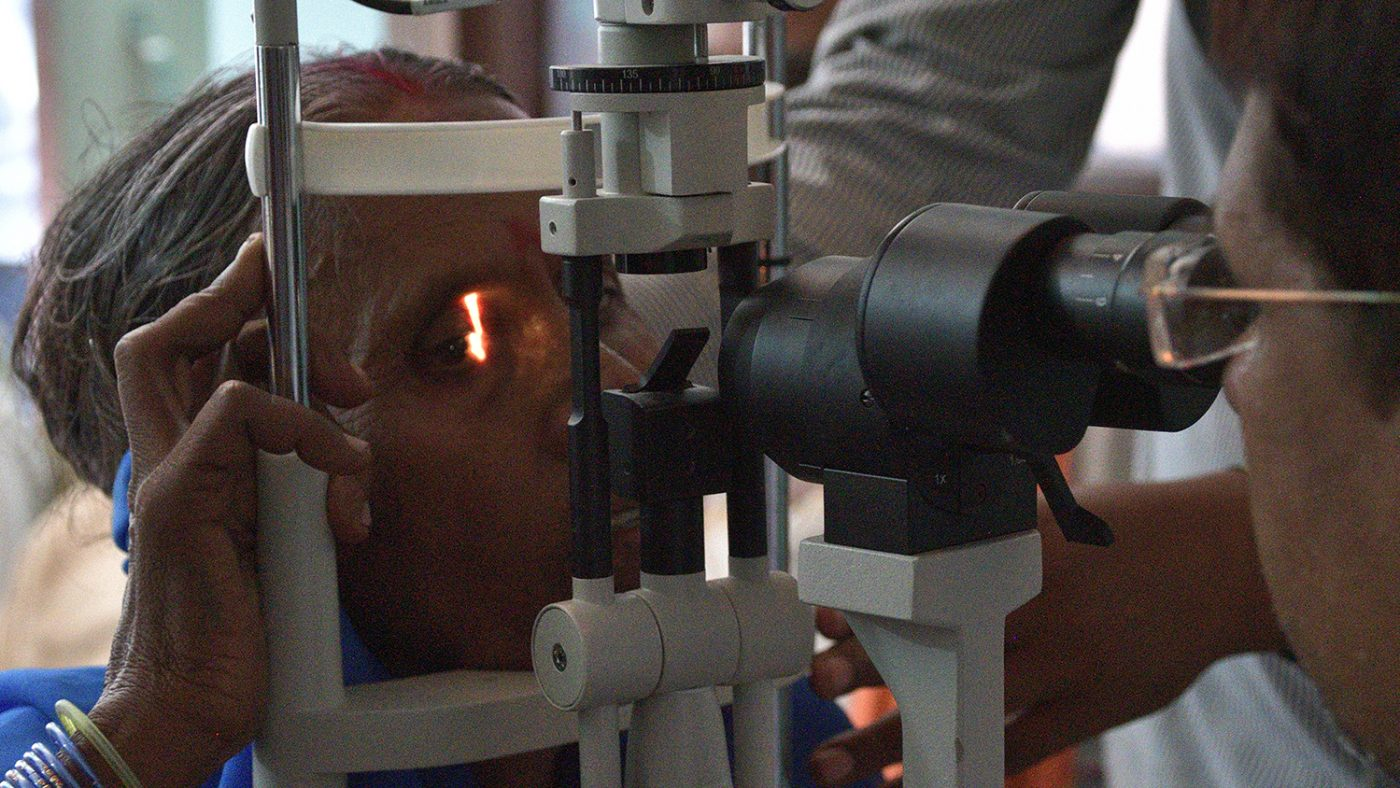 A woman has her eyes examined by an eye specialist, who shines a light into her eye.