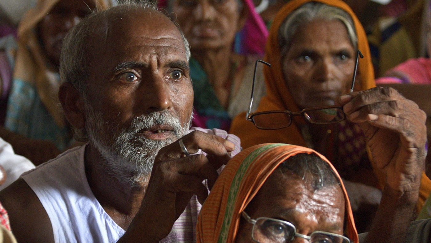 A man waves his spectacles in the air during an eye screening session in Bihar.