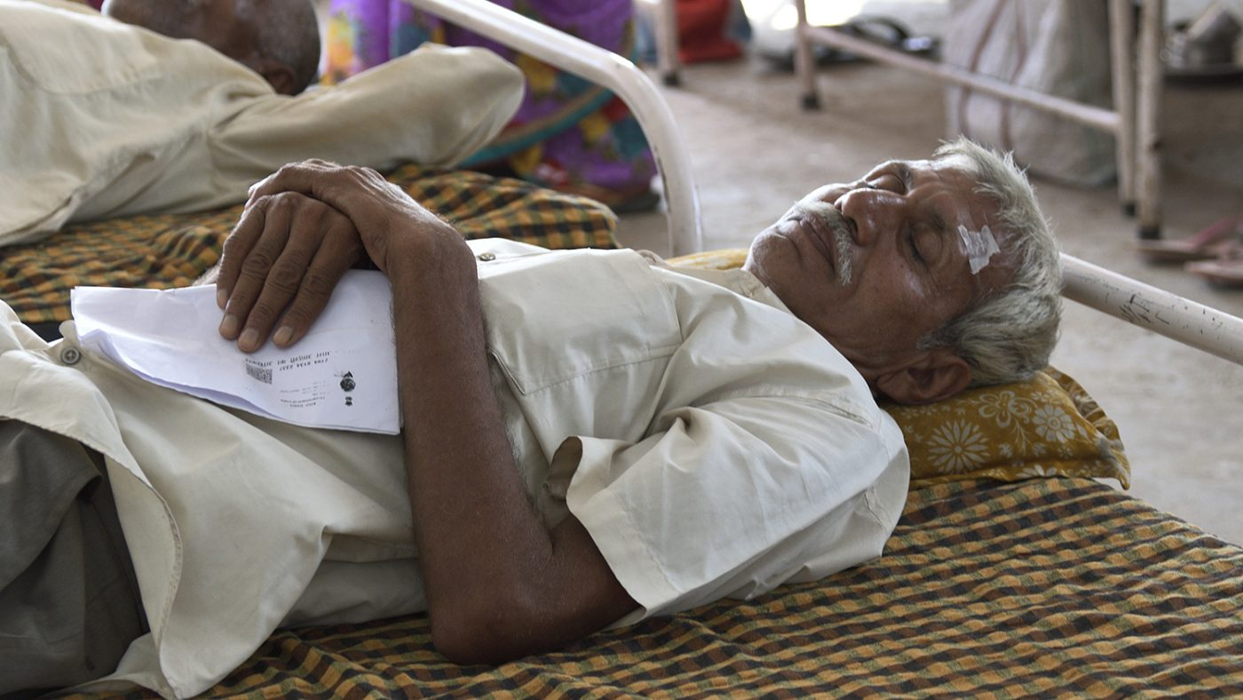 A patient lies sleeping in a hospital bed, clutching his papers.