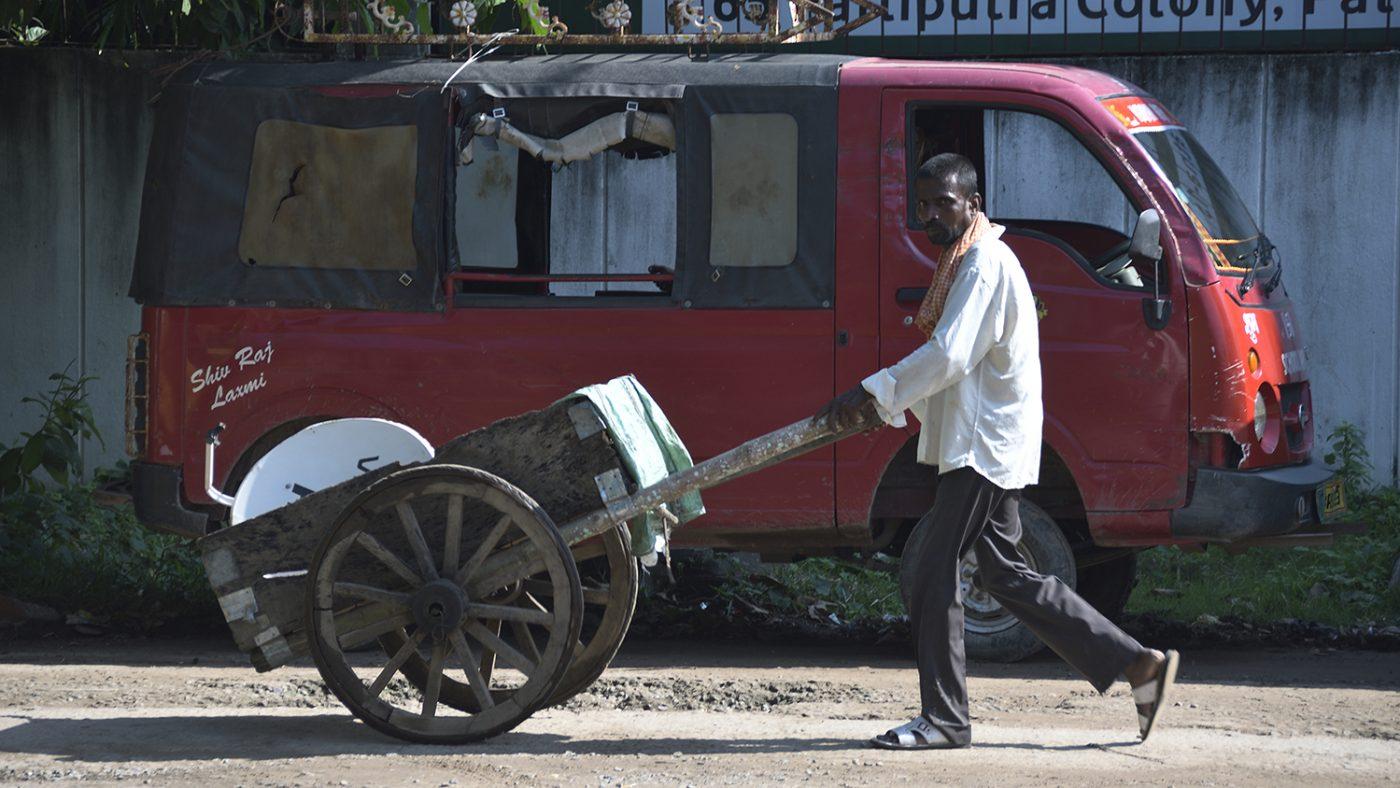 A man pushes a barrow down the dirt road in Bihar, India.