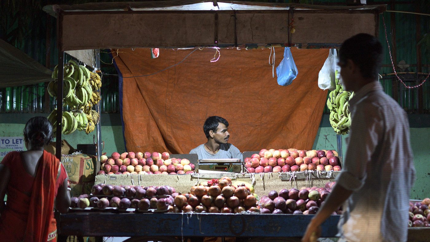 A stallholder sits behind his market stall selling apples.