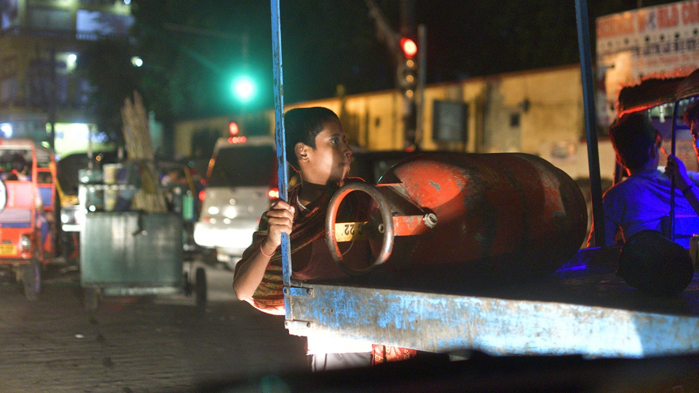 A child is lit up by street lights as he rides on a truck.