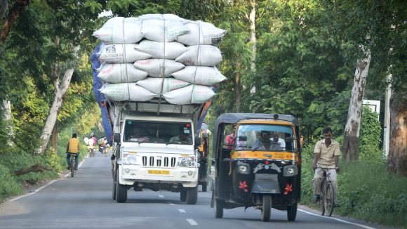 A truck stacked high with bags of rice travels down the road in Bihar, India.