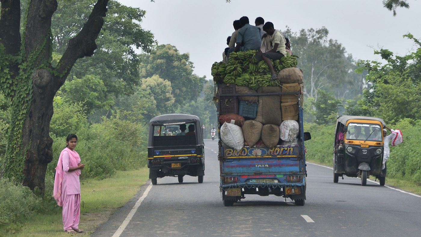 A truck is stacked high with produce and passengers.