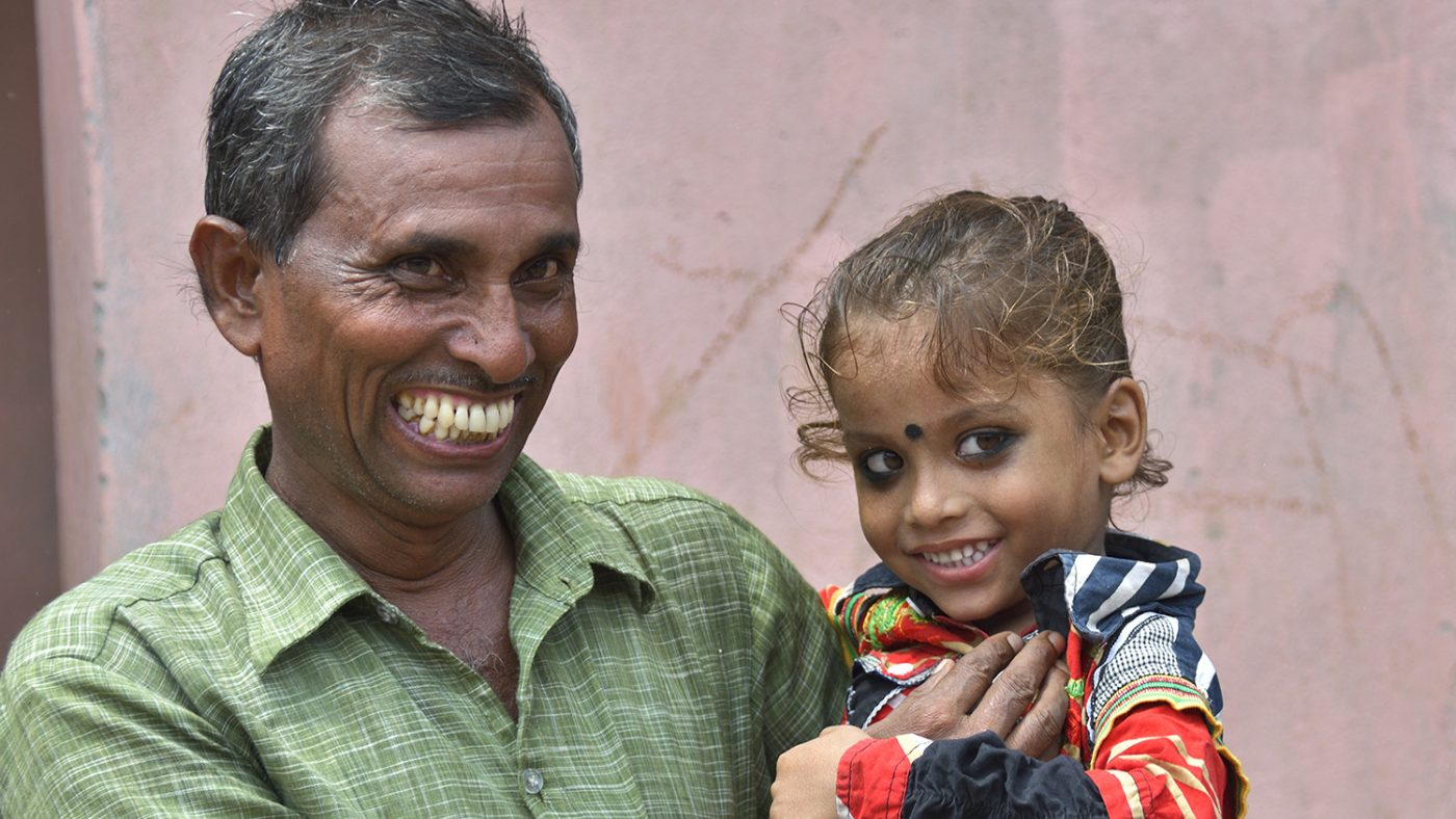 A father holds his daughter as they both smile for the camera.