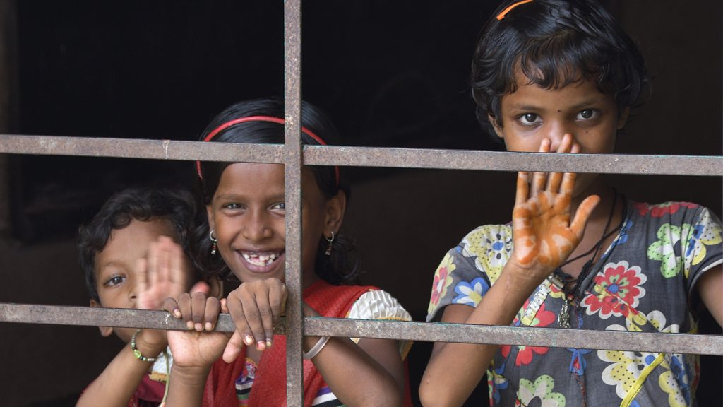 A group of girls smile as they stand behind railings.