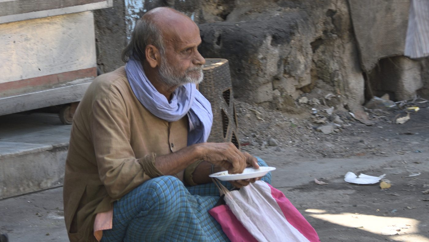 An elderly man sits by the side of the road holding a plastic plate.