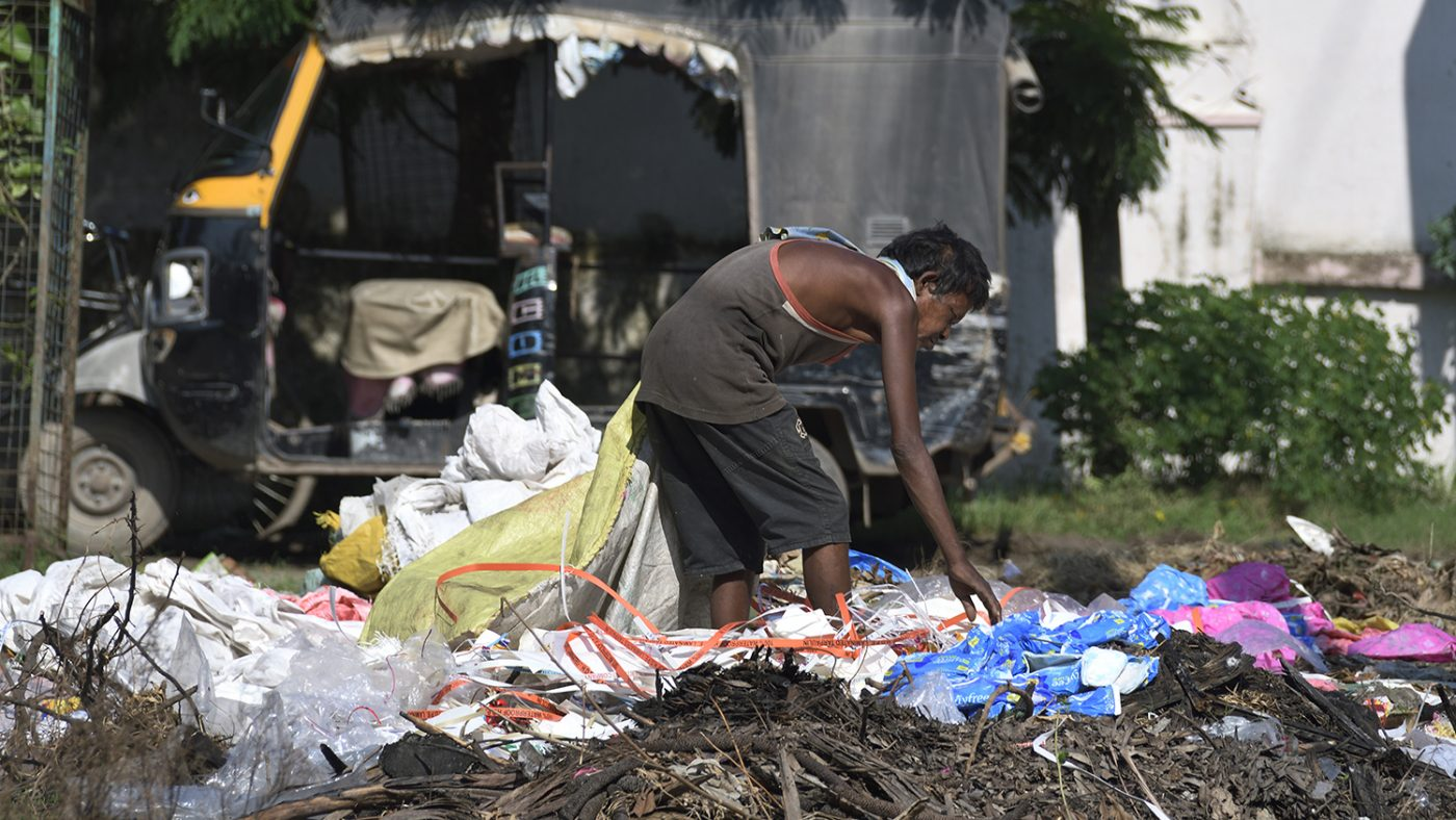 A man digs through a rubbish heap looking for valuables.