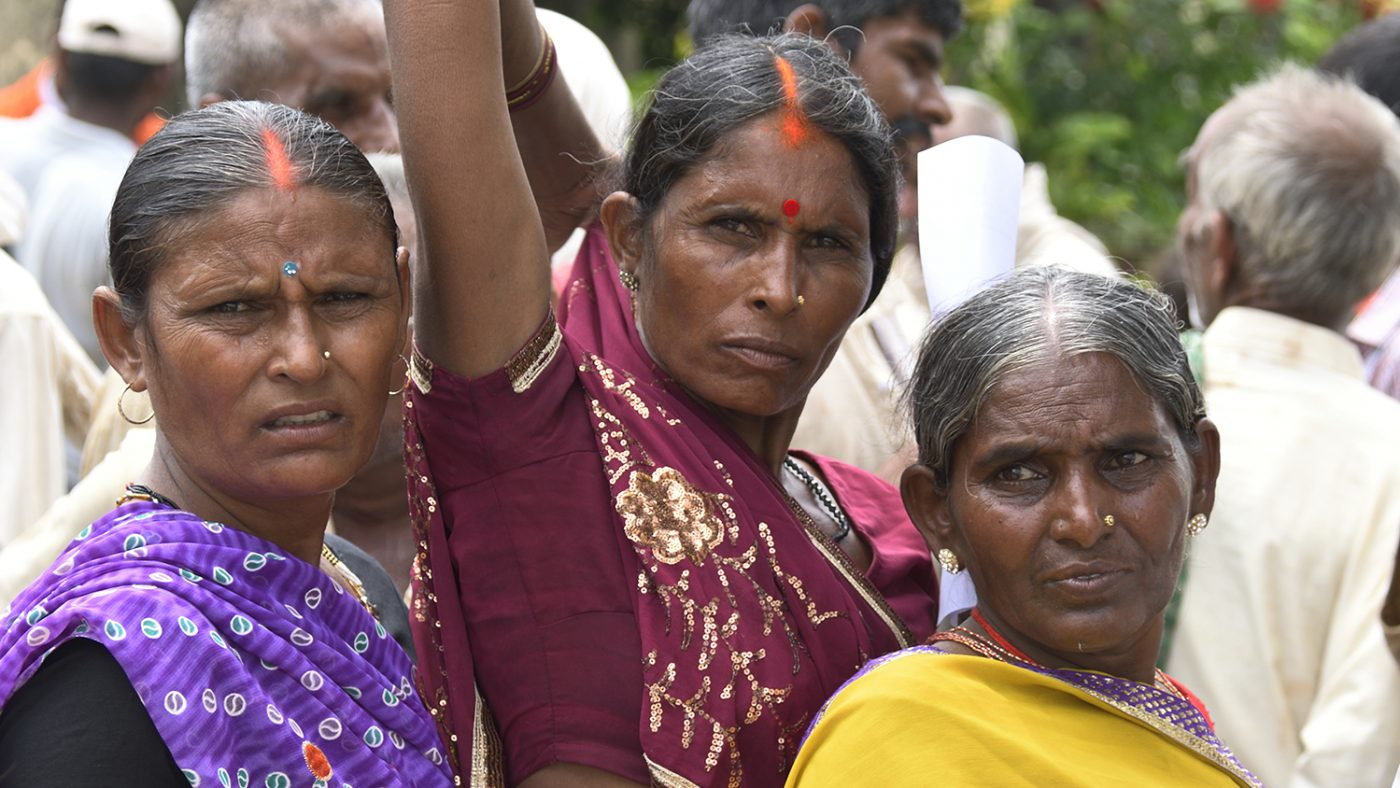 Three women wearing colourful saris.