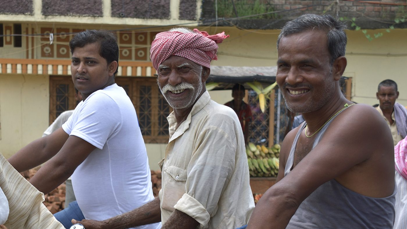 A group of men smile at the camera in Bihar.