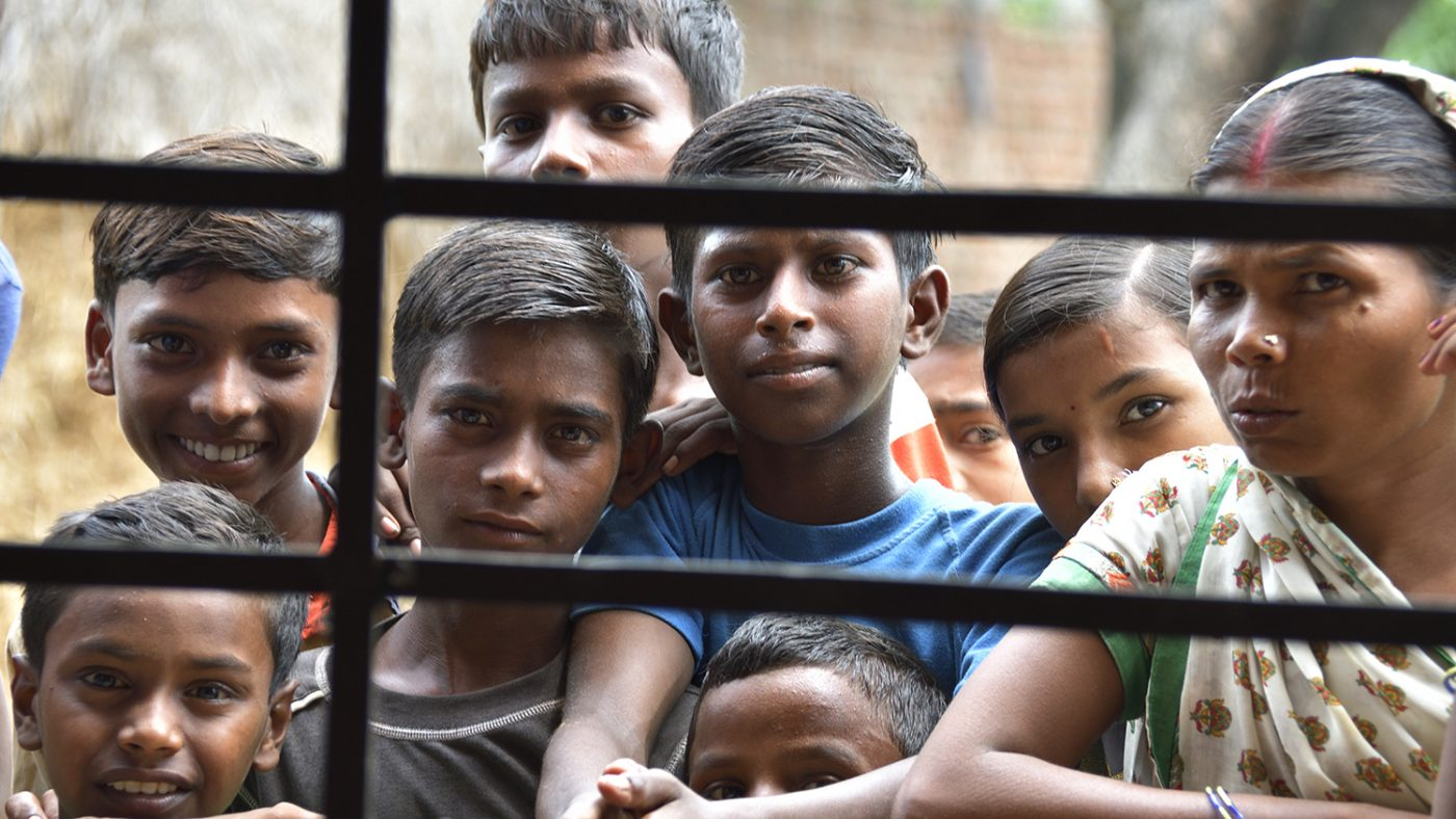 A group of children smile behind railings.