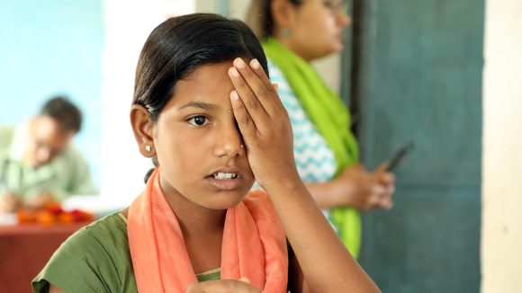 A girl in India holds one hand over her eye during a sight test at school.