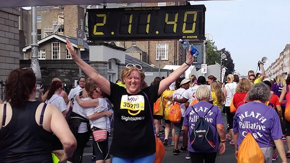 Jackie Carroll raises her arms at the finish line of the VHI Mini Marathon, standing underneath the clock reading 2:11:40.