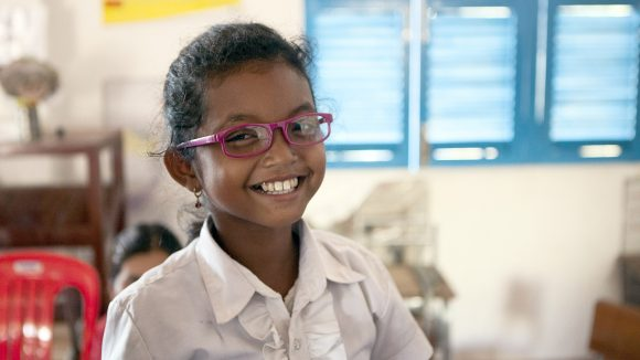 11-year-old Pouk Sreyneth smiles while wearing her new glasses.
