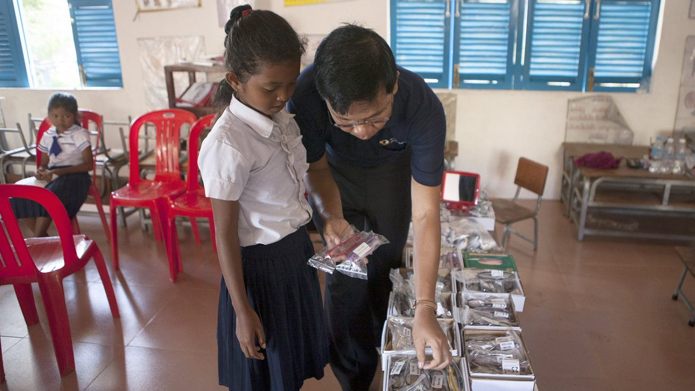 A pupil in Cambodia chooses some new glasses.