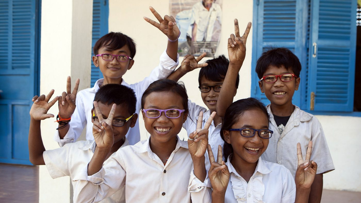 Students from Wat Run primary school in Cambodia smile and laugh while wearing their new glasses.