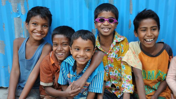 A group of smiling children in Bangladesh, some wearing spectacles.
