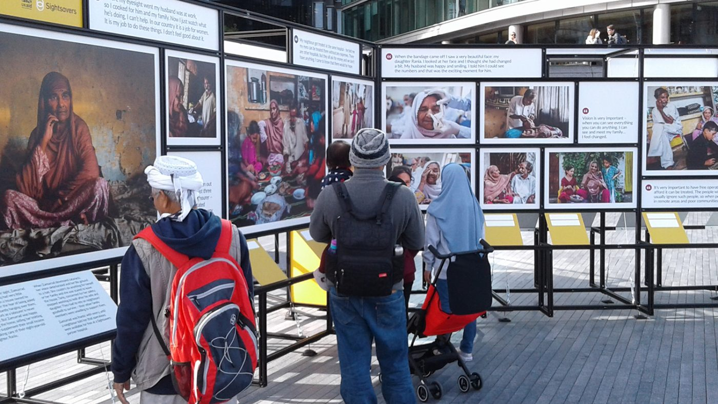 Passers-by look at the Sightsavers photo exhibition.