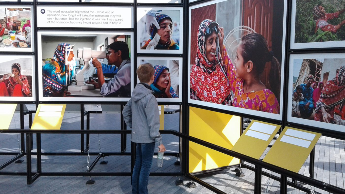 A passer-by looks at photos from Sightsavers' exhibition on London's South Bank.