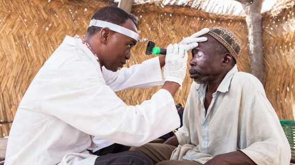 A patient has his eyes examined by an eye health worker in Mali.