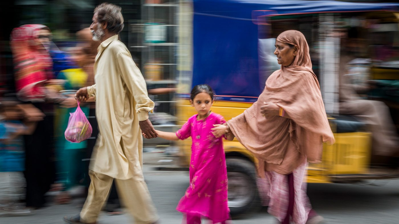 Zamurrad relies on her daughter and husband to guide her across a busy road.