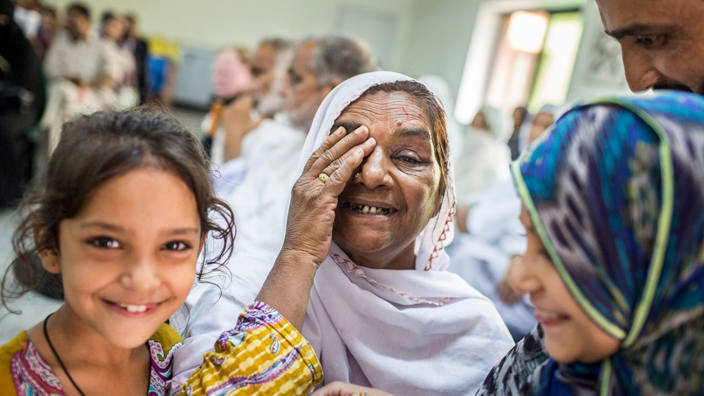 Zamurrad holds a hand up to her eye, while both her and her daughter smile at the camera.