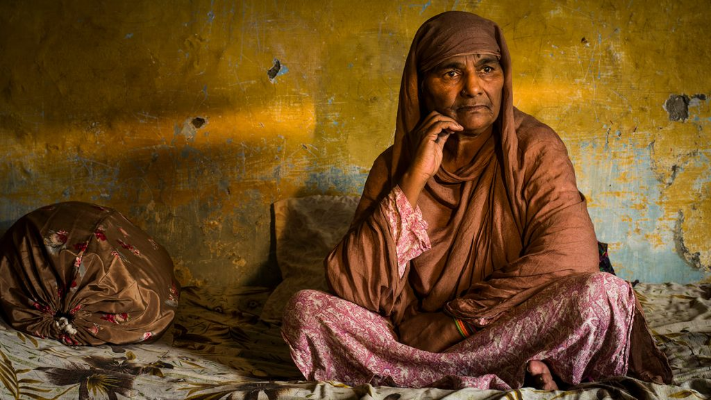 Zamurrad sits alone in her home in Pakistan.